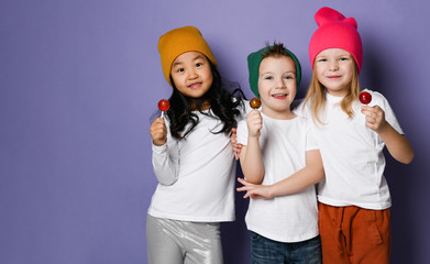 Gang of three cool kids in white t-shirts, colorful hats and pants posing with lollipops hugging together on purple Fototapete