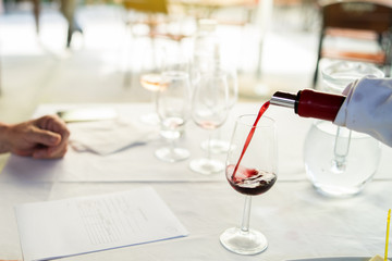Man sommelier waiter pouring wine in the drinking glass at the testing ceremony event for the expert to test it and give marks about the quality to the degustation card