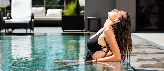 panoramic shot of attractive sexy woman in swimming suit posing in pool on resort