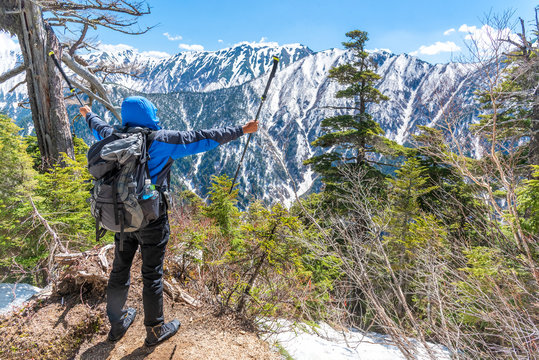 Hiker man hold trekking pole and spreading hand when see snow mountain range at view point.