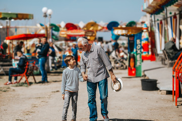 Grandfather and grandson having fun and spending good quality time together in amusement park.