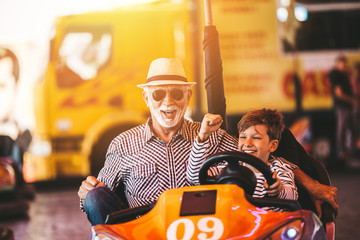 Grandfather and grandson having fun and spending good quality time together in amusement park. They...