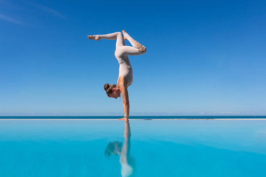 Charming young woman in a suit standing in Adho Mukha Vrksasana exercise, Downward facing Tree pose on edge of pool against blue sky. The concept of improving blood circulation in the head. Copyspace