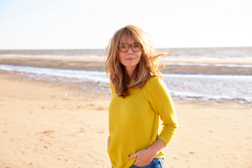 Middle aged woman with frizzy hair walking on the beach
