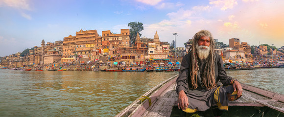 Indian sadhu on a wooden boat overlooking panoramic view of ancient Varanasi city architecture with Ganges river ghat Wall mural
