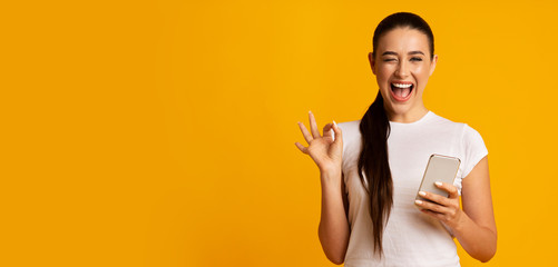 Woman Holding Phone And Gesturing OK Sign Over Yellow Background Wall mural