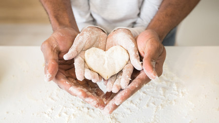Zelfklevend Fotobehang Bakkerij Afro man hands holding child hands with heart shaped pastry