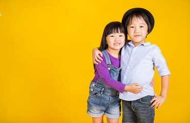 Portrait of young happy little asian boy girl in on yellow background. Education for preschool toddler, brother and sister lifestyle back to school together concept.