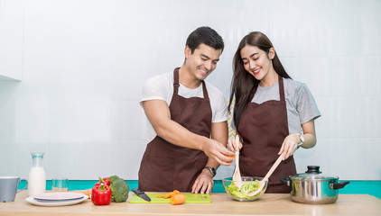 Portrait of asian couple cooking food with pan in the kitchen. Happy asian family with father mather, family's day, together healthcare cooking food concept