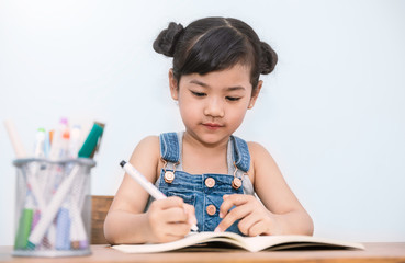 Portrait of little cute asian girl holding pencil writing in note book. Fun learning by doing activity toddler early childhood education homework school concept.