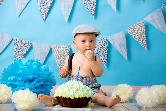 Little baby boy, celebrating his first birthday with smash cake party, studio isolated shot on blue