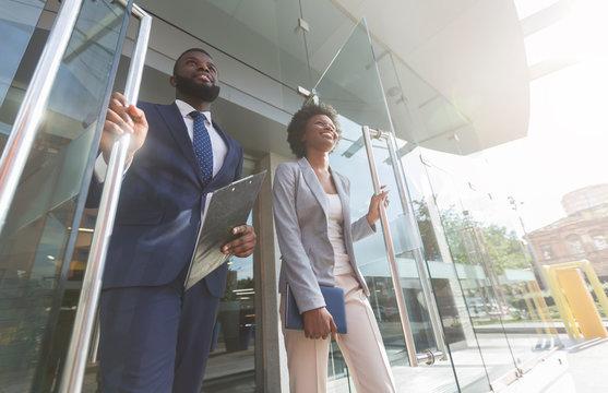 Confident african business people walking out of modern office center