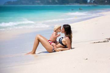 Mother and child playing at tropical beach. Family sea summer vacation. Mom and kid, toddler boy, play in the water. Ocean and water fun for parent and kids Wall mural