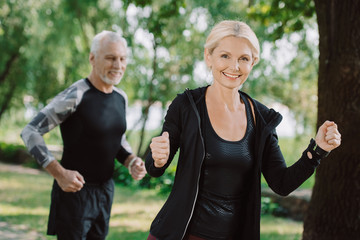 cheerful mature sportsman and sportswoman jogging in park together