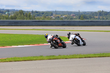 Two riders on motorcycles riding on the race track