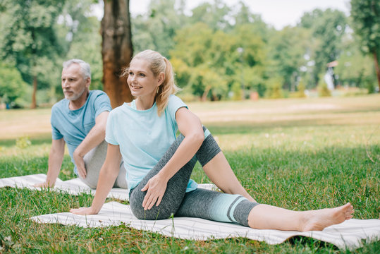 smiling mature man and woman practicing yoga while sitting on yoga mats in park