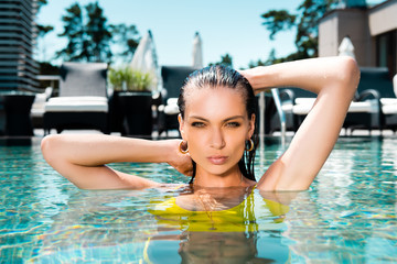 beautiful sexy woman in swimming suit with hands on head posing in pool on resort