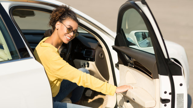 Happy afro woman getting out of car, opening door