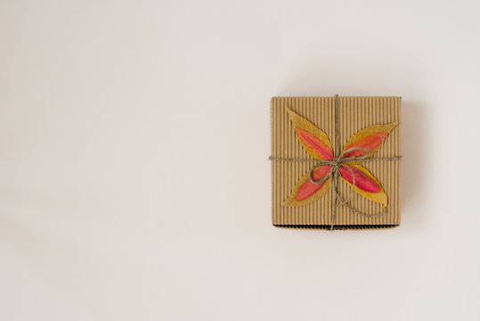 craft gift box, tied with string with a bow and autumn fallen leaves on a beige background. Birthday gift for people born in autumn. The view from the top. Copy space