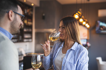 Couple in a restaurant tasting wine
