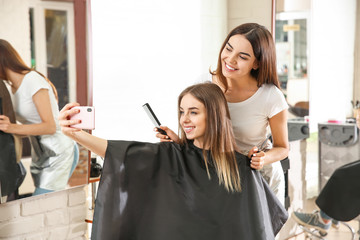 Young woman taking selfie with her hairdresser in salon