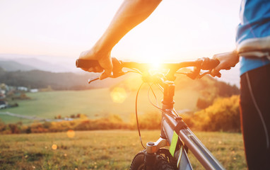 Man hands on the bike steering wheel close up image. Man with bike stay on the top of hill and enjoying the sunset.
