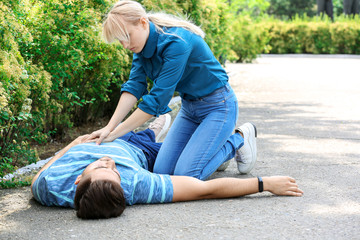 Woman giving CPR to unconscious man outdoors