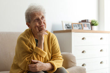 Thoughtful elderly woman on sofa at home