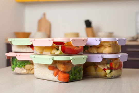 Boxes with prepared meals on table against blurred background