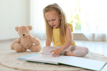 Pretty little girl with book and teddy bear on floor in room