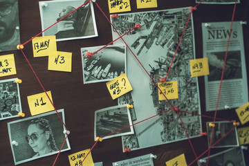 Detective board with photos of suspected criminals, crime scenes and evidence with red threads, selective focus