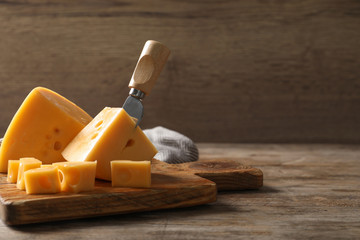Serving board with delicious cheese on wooden table, space for text