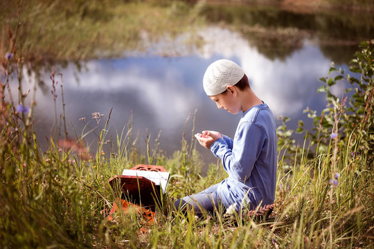 A Muslim child prays in nature near a beautiful lake.
