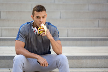 Young latin man eating banana fruit runner fitness copyspace copy space sports training