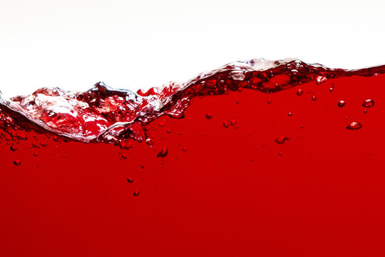red bright liquid with splash and bubbles isolated on white