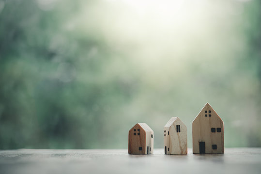 Miniature wooden houses on table with green nature background and sunray. Building blocks arranged in row