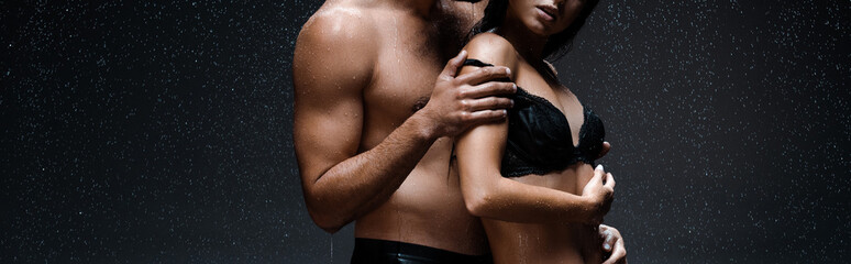 panoramic shot of sexy man hugging woman in lingerie under raindrops on black
