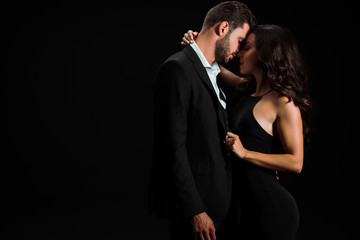 attractive woman touching suit of man while standing isolated on black