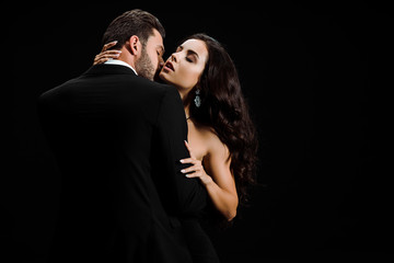 passionate man in suit kissing attractive woman isolated on black