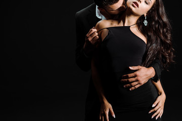 cropped view of passionate man kissing woman in dress isolated on black