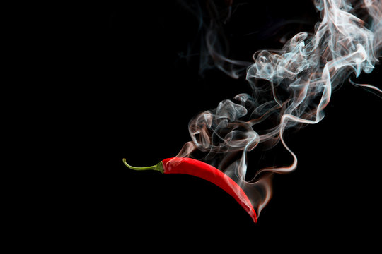 Red chili with smoke on a black background, the concept of spicy