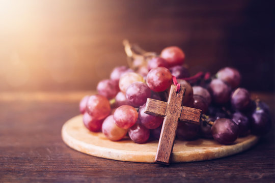 Close-up of wooden cross lean over grape on wood plate against window light  on wooden table, christian background with copy space