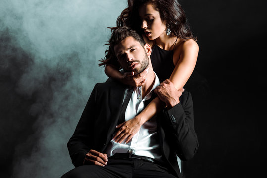 passionate young woman standing and hugging handsome bearded man on black with smoke