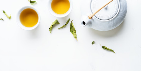 Asian tea concept, two white cups of tea and teapot surrounded with green tea dry leaves view from above, space for a text on white background. Long wide banner Wall mural