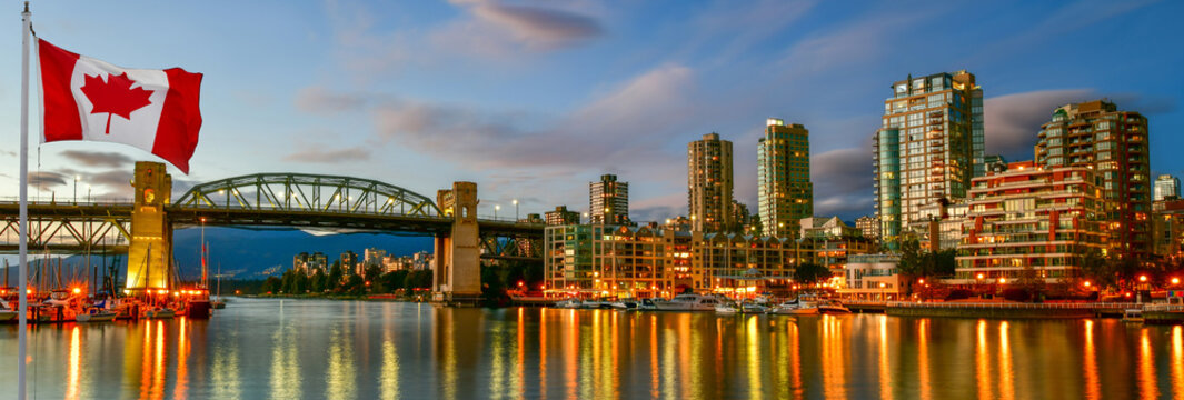 Canadian flag in front of view Granville island near Burrard Street Bridge at twilight in Vancouver,Canada