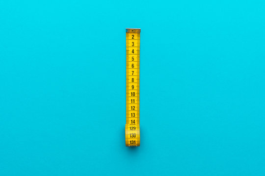 Top view of yellow soft measuring tape. Minimalist flat lay image of tape measure with metric scale over turquoise blue background with central composition