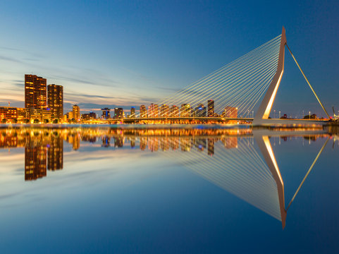 The Erasmusbrug and the Rotterdam skyline by night with a reflection in the water, a famous landmark in the Netherlands and travel destination