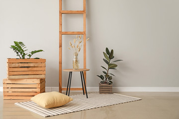 Table with wooden boxes and ladder near light wall in room