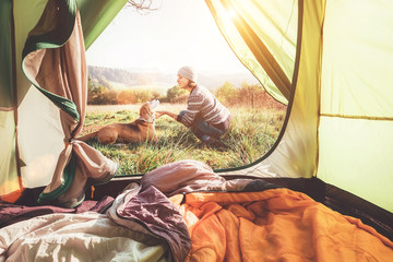 Woman pand her dog tender scene near the camping tent. Active leisure, traveling with pet concept image