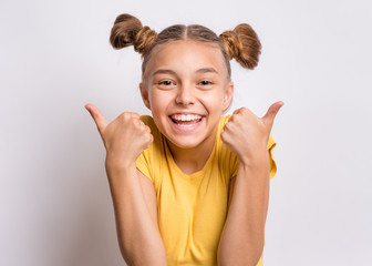 Portrait of teen girl making Thumb up Gesture, on gray background. Beautiful caucasian young teenager smiling. Happy cute child showing success sign. Fototapete